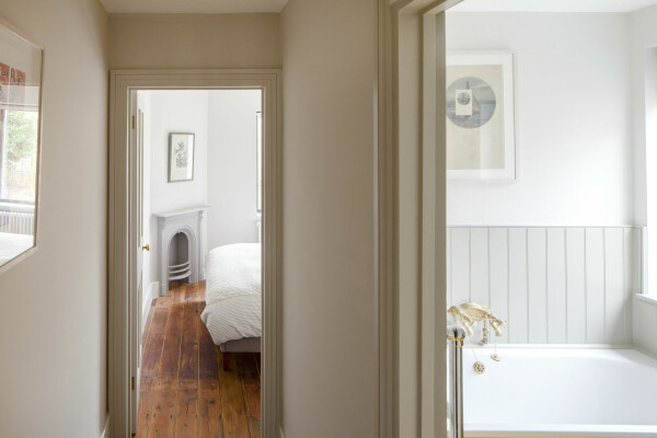 Hallway with pale, earthy paint tones looking through to a bedroom and a bathroom