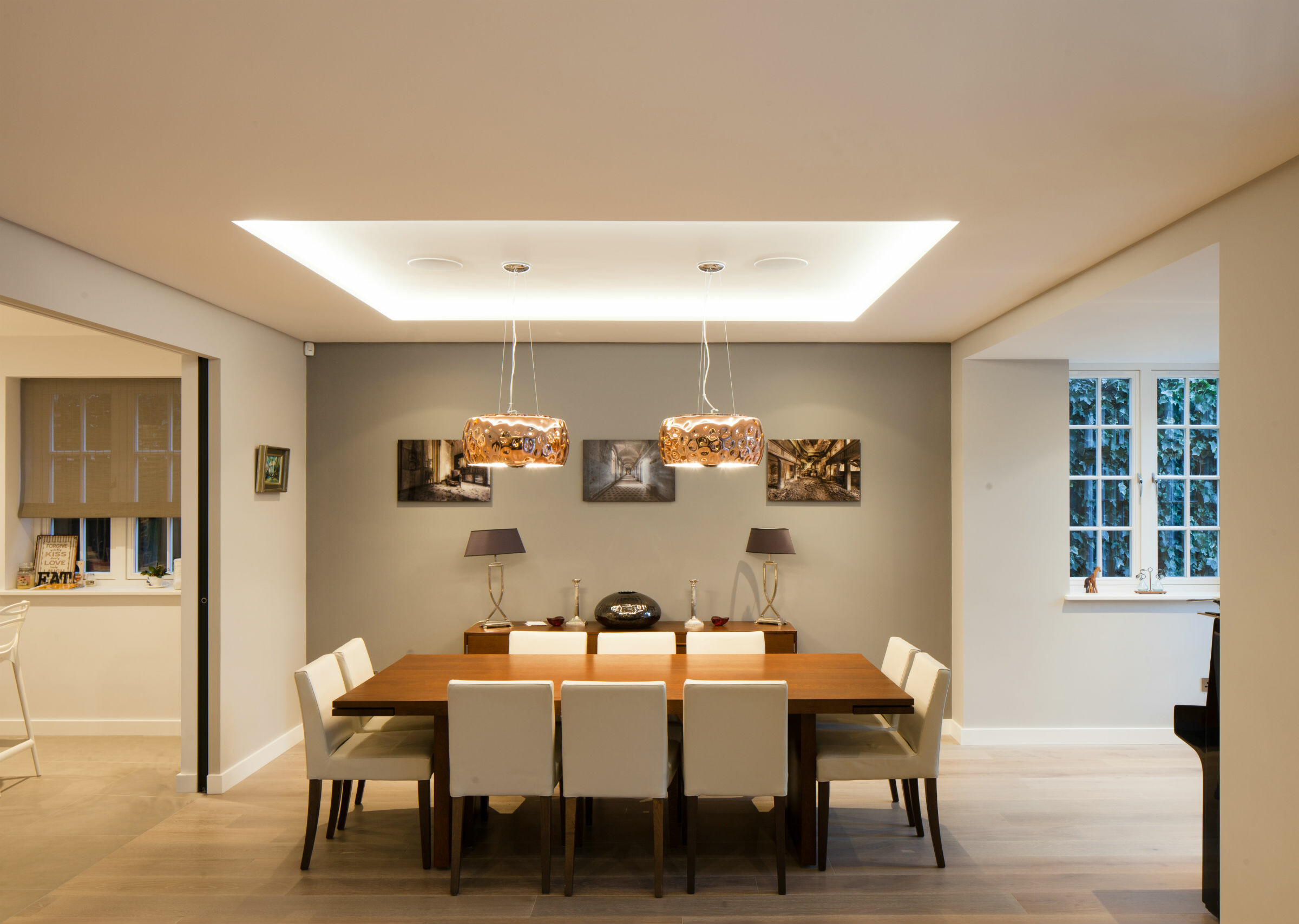 Dining room with large table with pendant lights above