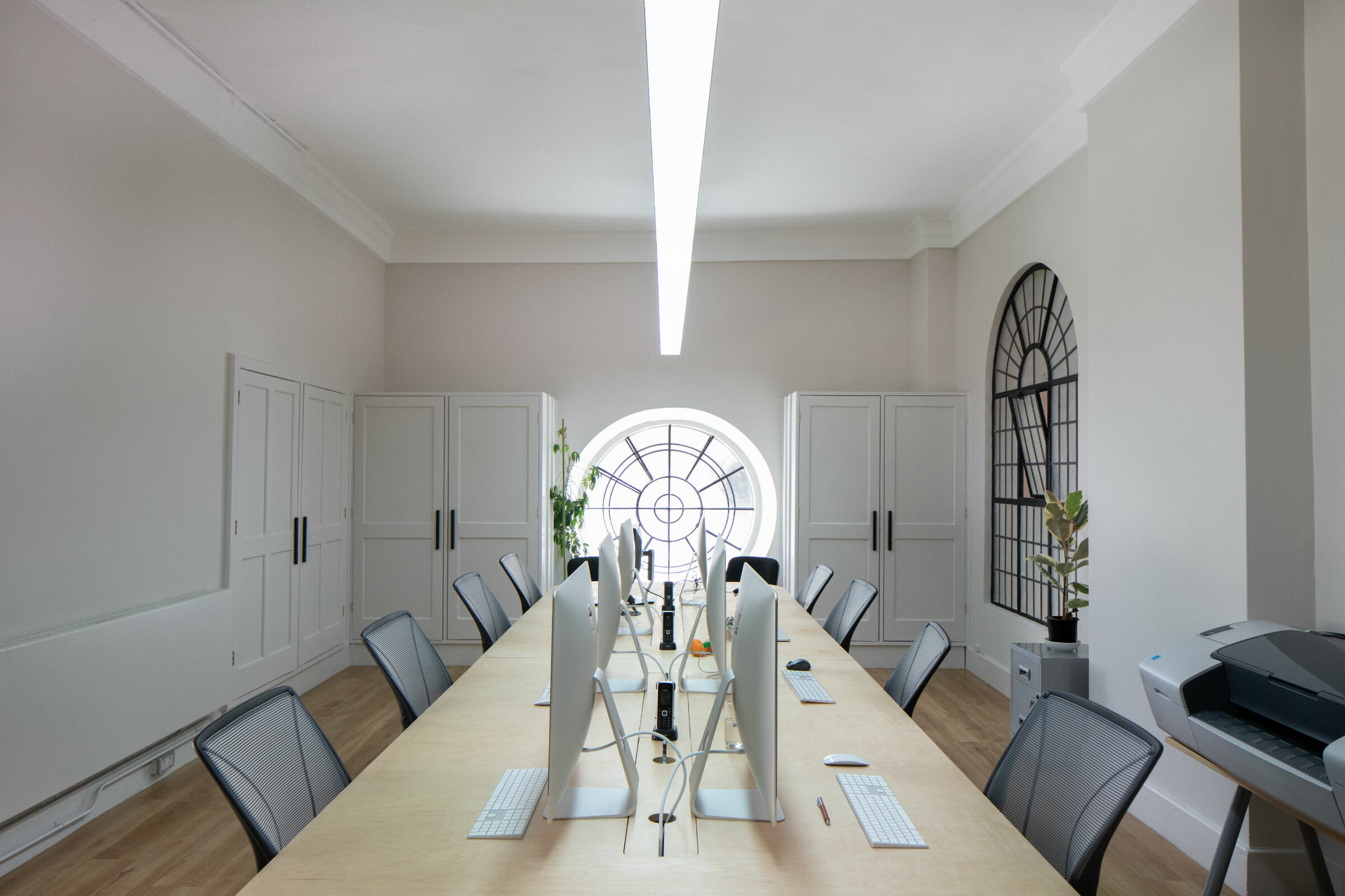 Long desk with iMacs with a round leaded window at the end