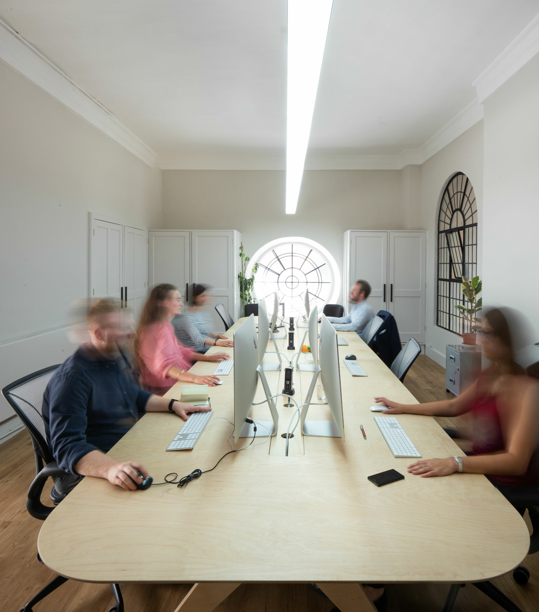 People working at a desk, they are blurred due to slow shutter speed